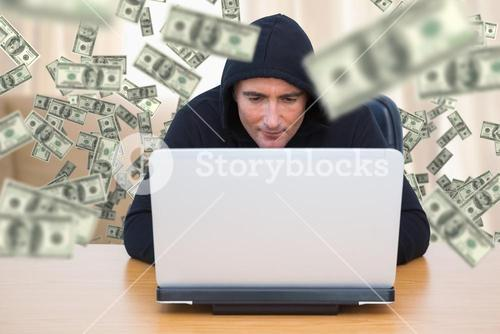 Composite image of smiling thief in hood jacket using laptop and credit card