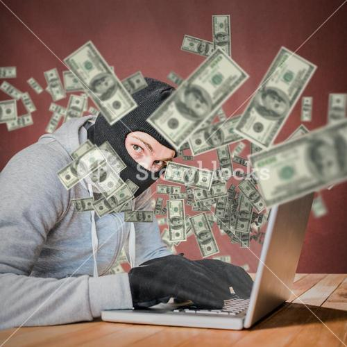 Composite image of focused thief with hood typing on laptop