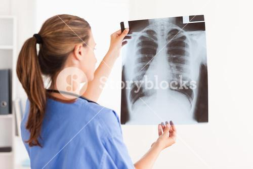 Gorgeous brunette doctor with stethoscope looking at a xray