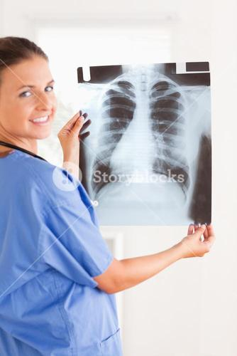 Charming doctor smiling at the camera holding a xray