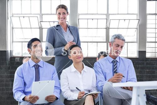 Composite image of business team taking a note during a meeting