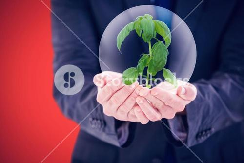 Composite image of scientist holding basil plant