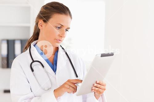 Charming doctor having a stethoscope around her neck looking at a file
