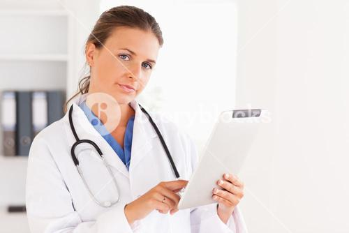 Charming doctor having a stethoscope around her neck pointing at a file looking at the camera