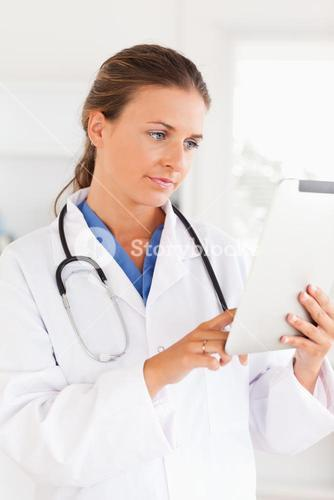 Charming doctor with a stethoscope pointing at a file