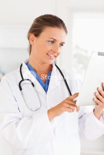 Smiling doctor with a stethoscope pointing at a file