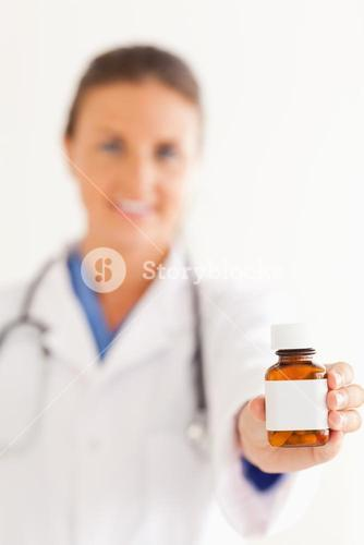 Close up of a cute doctor handing over some pills