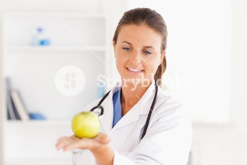 Smiling doctor with stethoscope holding an apple