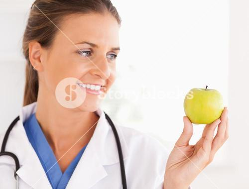 Close up of a smiling doctor with stethoscope looking at an apple