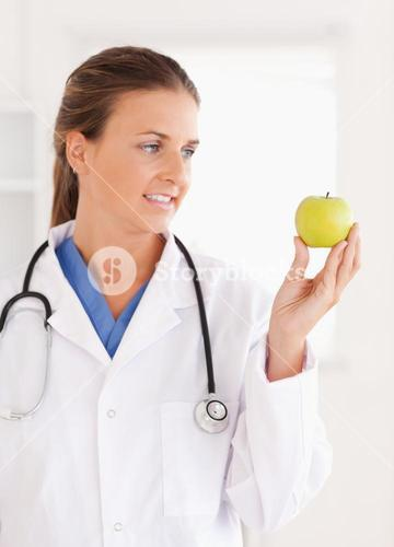 Gorgeous doctor looking at a green apple