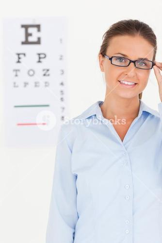 Good looking brunette eye specialist wearing glasses looking into the camera
