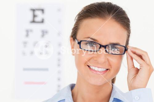 Close up of a good looking brunette eye specialist wearing glasses looking into the camera