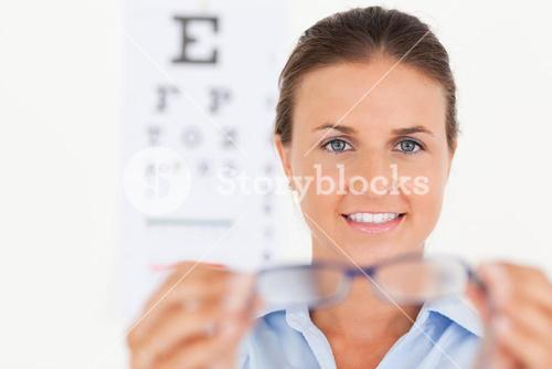 Portrait of a brunette eye specialist handing out glasses looking into the camera