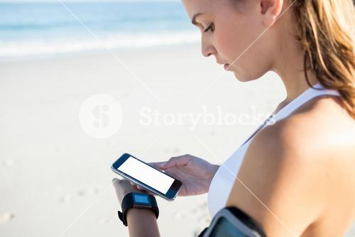 Smiling woman in sportswear texting on smartphone