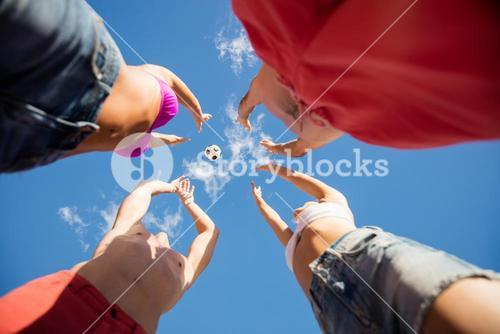 Low angle view of friends playing with a ball