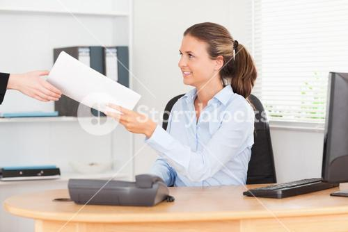 smiling businesswoman receiving a pile of paper