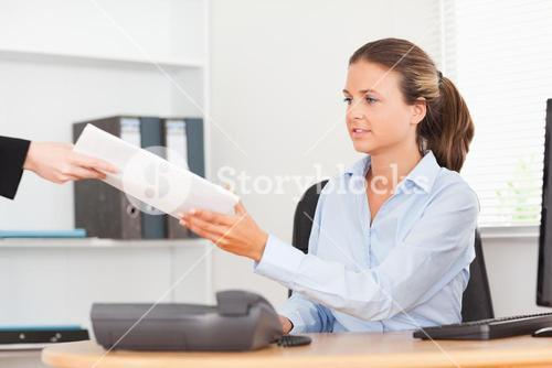 stressed businesswoman receiving a pile of paper