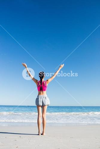 Woman with hands up on the beach