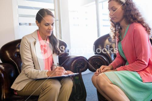 Beautiful young woman discussing with psychologist