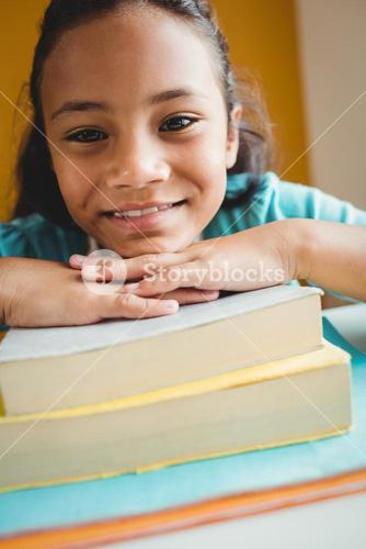 Girl leaning her head on pile of books