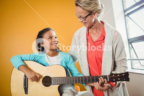 Girl learning how to play the guitar