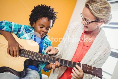 Boy learning how to play the guitar