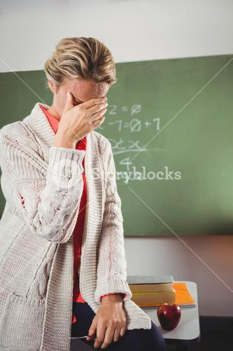 Teacher crying in front of blackboard