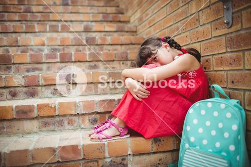 Sad brunette girl seated against a brick wall