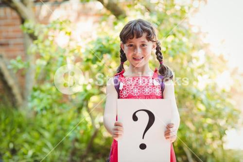 Girl holding a sign with a question mark