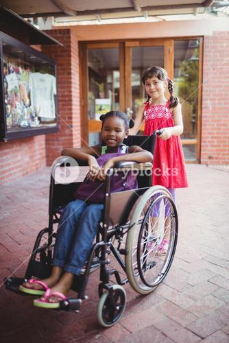 Girl pushing a friend in a wheelchair on a sunny day