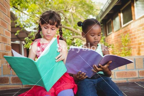 Two children looking their book