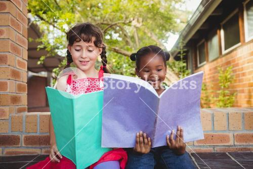Two children holding a book