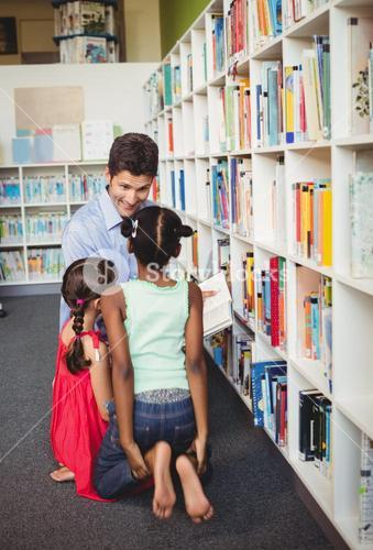 Man reading a book for two children