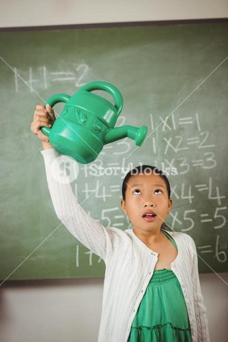 Schoolgirl using a watering can