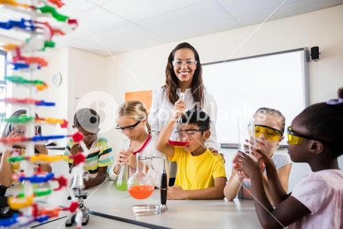 A teacher posing with pupils doing science