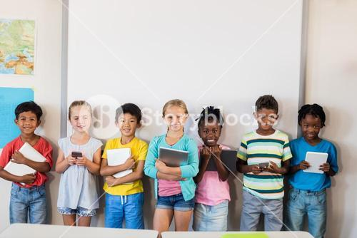 Smiling pupils standing with technology