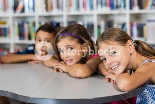 three pupils posing for the camera at desk