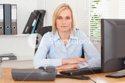 Serious woman sitting behind a desk