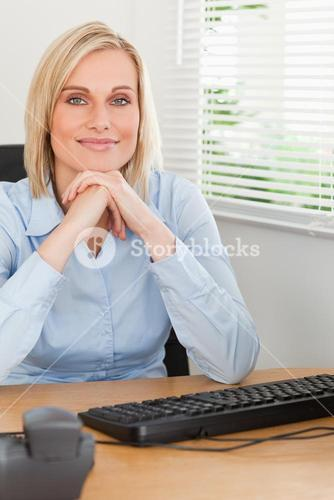 Charming blonde woman with chin on her hands behind a desk
