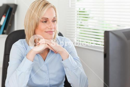 Cute blonde woman with chin on her hands behind a desk looking at screen