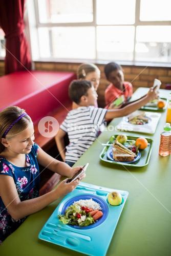 Children using technology during lunch