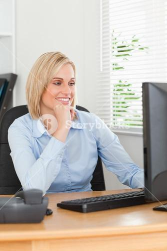 Smiling blonde woman with chin on hand behind a desk looking at screen