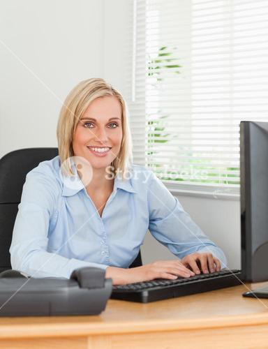 Working blonde woman in front of a screen looks into camera