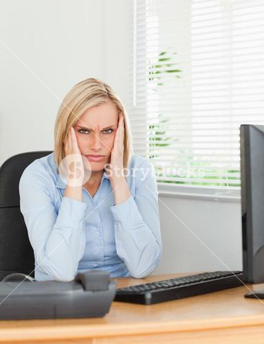 Frustrated working woman looking into camera