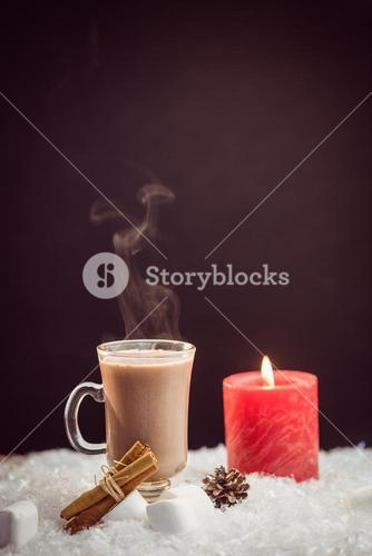 close up view of composite image of hot chocolate and candle
