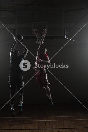 Basketball player shooting a basketball with a defender