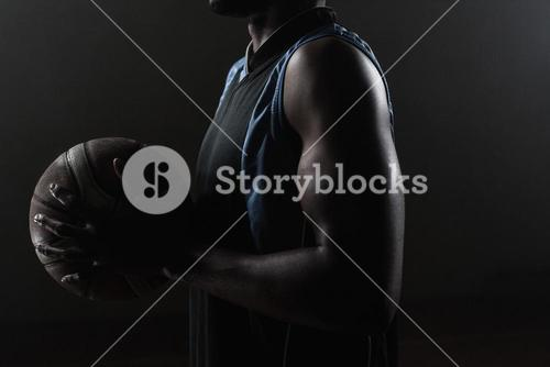 Zoom on a side of  a basketball player holding a basketball