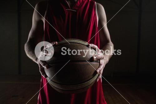 Close up on basketball player holding a ball