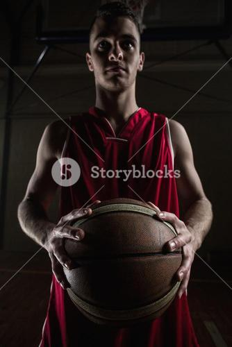 Portrait of basketball player unsmiling and holding a basketball