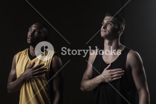 Portrait of basketball players looking up and putting hand on heart